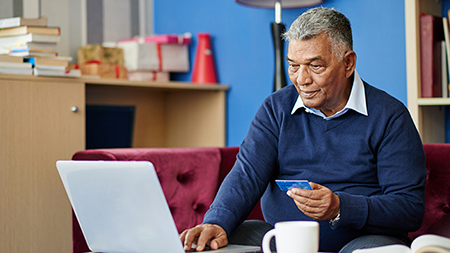 Financial health and wellness-man sitting at laptop computer holding a credit card.
