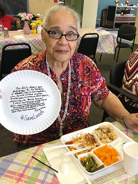Rose Centers participant eating lunch and holding up a paper plate explaining why Rose Center meals matter for the  hashtag SaveLunch campaign