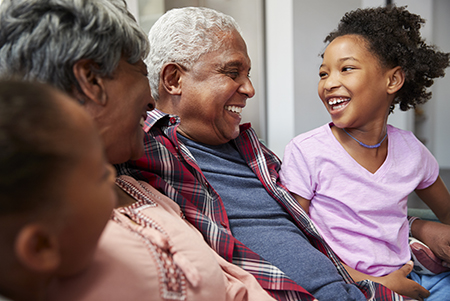 Behavioral Health Services- Grandparents sitting on the couch with their granddaughters
